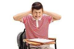 Estudiante adolescente que se sienta en una silla y que cubre sus oídos Foto de archivo