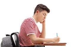 Estudiante adolescente que se sienta en una silla y que toma notas Foto de archivo libre de regalías