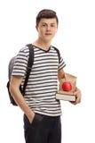Estudiante adolescente que sostiene libros y un bocado Imagenes de archivo