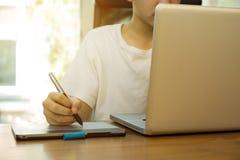 Estudiante adolescente que trabaja en el ordenador portátil en la tabla de madera Fotografía de archivo
