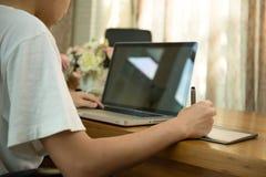 Estudiante adolescente que trabaja en el ordenador portátil en la tabla de madera Imágenes de archivo libres de regalías