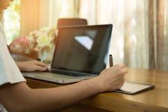 Estudiante adolescente que trabaja en el ordenador portátil en la tabla de madera Fotos de archivo