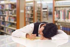Estudiante adolescente Stressed de la raza mixta y frustrado en biblioteca Foto de archivo