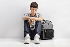 Estudiante adolescente triste que se inclina contra una pared gris Foto de archivo