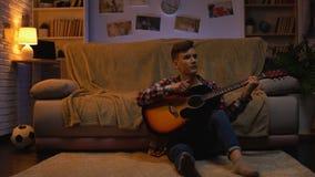 Estudiante adolescente zurdo que toca la guitarra en casa que se relaja después de la afición de las conferencias almacen de metraje de vídeo