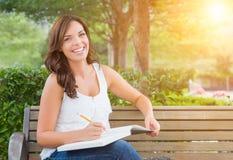 Estudiante adulto joven con el lápiz en banco al aire libre Fotos de archivo