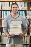 Estudiante adulto que presenta sosteniendo una pila de libros Foto de archivo libre de regalías