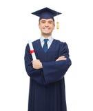 Estudiante adulto sonriente en birrete con el diploma Imagen de archivo
