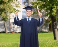 Estudiante adulto sonriente en birrete con el diploma Fotos de archivo
