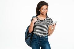 Estudiante africana joven con música que escucha de la mochila a través de los auriculares Fotos de archivo
