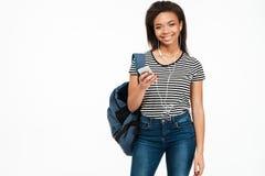 Estudiante africana joven con música que escucha de la mochila a través de los auriculares Imagen de archivo libre de regalías