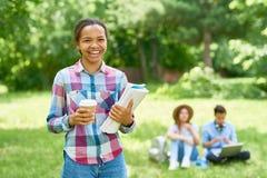 Estudiante africano alegre en césped del campus Fotografía de archivo libre de regalías