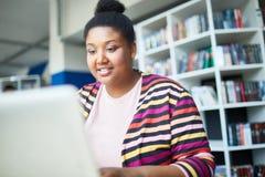 Estudiante africano alegre que lee el artículo en línea fotografía de archivo libre de regalías