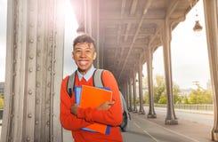Estudiante africano con los libros de texto en la calle de la ciudad Fotografía de archivo libre de regalías