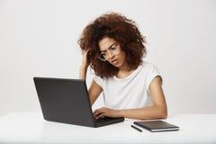 Estudiante africano joven cansado y del ucertain de la moda del diseño que piensa en su estudio que trabaja en el ordenador portá Imagenes de archivo