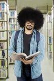 Estudiante africano que lee un libro en la biblioteca Fotografía de archivo libre de regalías