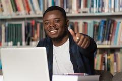 Estudiante africano In una biblioteca que muestra los pulgares para arriba Fotografía de archivo