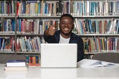 Estudiante africano In una biblioteca que muestra los pulgares para arriba Imagenes de archivo