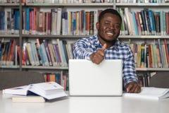 Estudiante africano In una biblioteca que muestra los pulgares para arriba Fotos de archivo libres de regalías