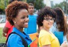 Estudiante afroamericano con la mujer caucásica joven en el campus de imagenes de archivo