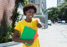 Estudiante afroamericano en una camisa amarilla que muestra el pulgar para arriba Imagenes de archivo