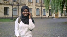 Estudiante afroamericano musulmán hermoso en hijab que se niega a afrontar universidad y que habla en el teléfono celular almacen de metraje de vídeo