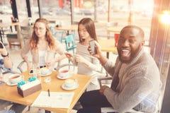 Estudiante afroamericano positivo que se sienta en el café Imagenes de archivo