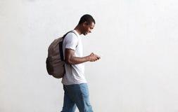Estudiante afroamericano que camina con el bolso y el teléfono móvil Foto de archivo