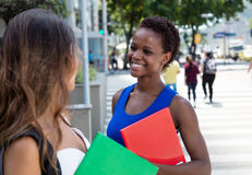 Estudiante afroamericano que habla con la novia caucásica Imagen de archivo