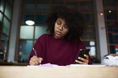 Estudiante afroamericano que se sienta en la tabla en el campus universitario que mira en la cámara que sostiene smartphone moder Foto de archivo libre de regalías