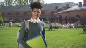 Estudiante afroamericano que tiene buen tiempo, presentando a lo largo de campus universitario almacen de video