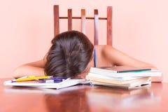 Estudiante agotado que duerme con su cabeza en una tabla Foto de archivo
