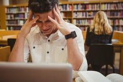 Estudiante agotador que lleva a cabo su cabeza foto de archivo