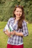 Estudiante alegre con los apoyos que sostienen los libros afuera Imagen de archivo libre de regalías