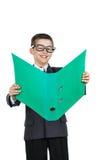 Estudiante alegre del muchacho que sostiene una carpeta con la tarea Muchacho en la sonrisa de los vidrios Foto de archivo libre de regalías