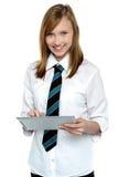 Estudiante alegre en traje de la escuela usando la PC de la tablilla Foto de archivo