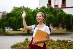 Estudiante alegre hermoso que sonríe, saludo, sosteniendo carpetas al aire libre, fondo del parque Fotos de archivo
