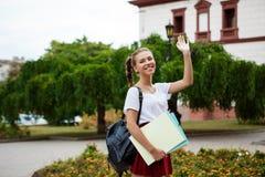 Estudiante alegre hermoso que sonríe, saludo, sosteniendo carpetas al aire libre, fondo del parque Imagen de archivo libre de regalías