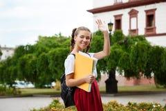 Estudiante alegre hermoso que sonríe, saludo, sosteniendo carpetas al aire libre, fondo del parque Imagen de archivo