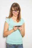 Estudiante alegre joven que usa el teléfono móvil Foto de archivo libre de regalías