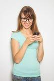 Estudiante alegre joven que usa el teléfono móvil Imagen de archivo libre de regalías