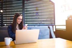 Estudiante alegre que usa el teléfono y el cuaderno de célula Fotografía de archivo