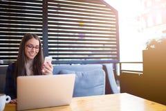 Estudiante alegre que usa el teléfono y el cuaderno de célula Imágenes de archivo libres de regalías