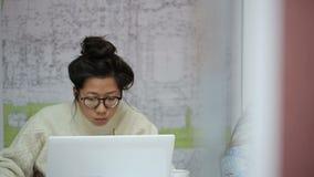 Estudiante asiática con los vidrios que lee una sinopsis en la colocación de comunicaciones urbanas metrajes
