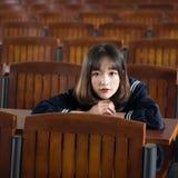 Estudiante asiática en uniforme escolar que aprende en la sala de clase Imagenes de archivo