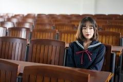 Estudiante asiática en uniforme escolar que aprende en la sala de clase Fotografía de archivo libre de regalías