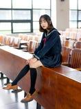 Estudiante asiática en uniforme escolar que aprende en la sala de clase Fotos de archivo libres de regalías