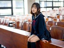 Estudiante asiática en uniforme escolar que aprende en la sala de clase Foto de archivo libre de regalías