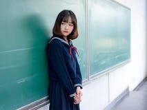 Estudiante asiática en uniforme escolar que aprende en la sala de clase Imagen de archivo