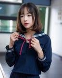 Estudiante asiática en uniforme escolar que aprende en la sala de clase Fotos de archivo
